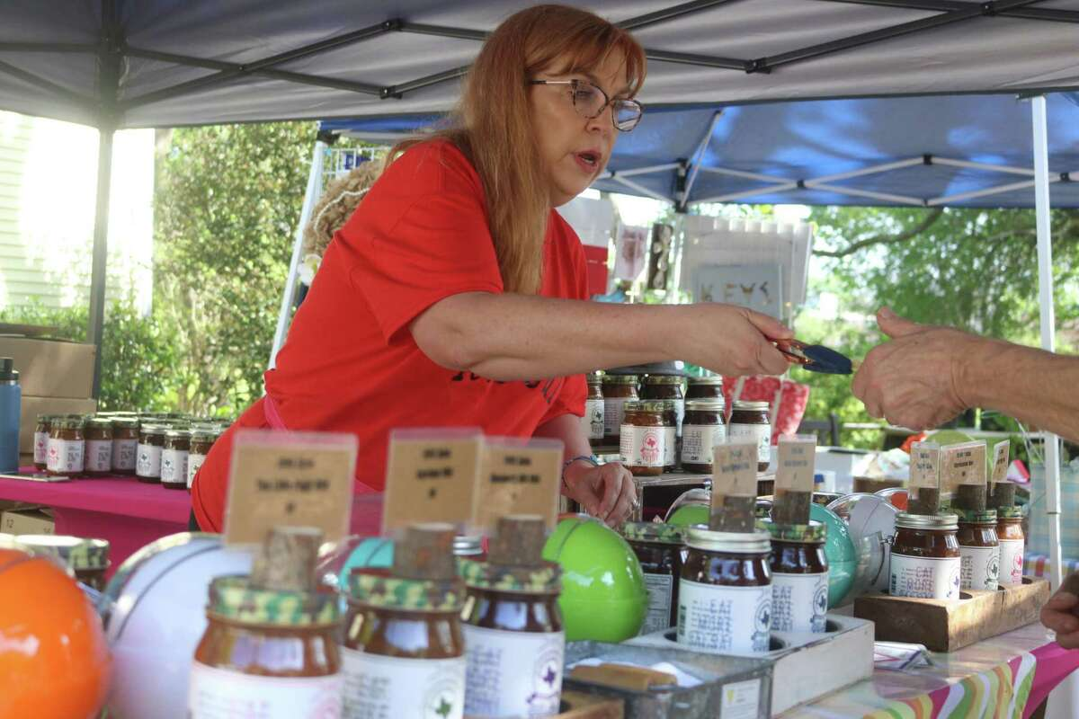 Suzanne Marquez hands a sample of 1893 Salsa to a potential customer during last Saturday's Heritage Gardeners Society Spring Market in Friendswood.