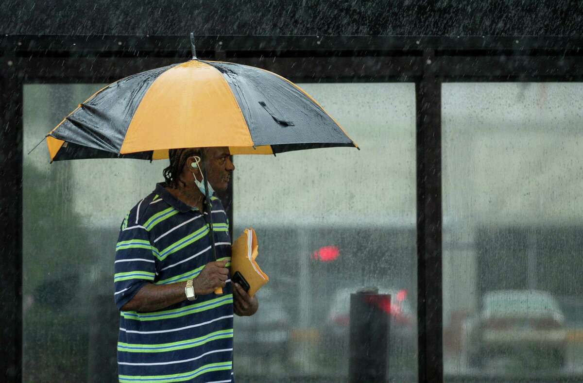 A man uses an umbrella to fend off heavy rain while waiting for a METRO bus on Richmond Avenue, on Friday, April 30, 2021, in Houston.