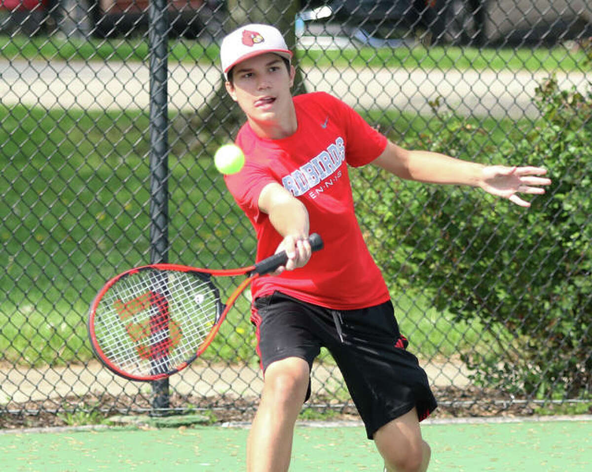 Alton sophomore Xavier Carter returns a shot during his No. 1 singles match against Marquette Catholic on Thursday at Moore Park's Simpson Tennis Center in Alton.