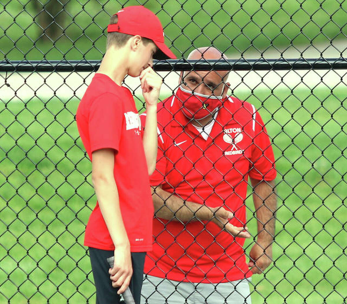 Alton coach Jesse Macias (right) talks with freshman James McKeever during a No. 4 singles match against Marquette Catholic on Thursday at Moore Park's Simpson Tennis Center in Alton.