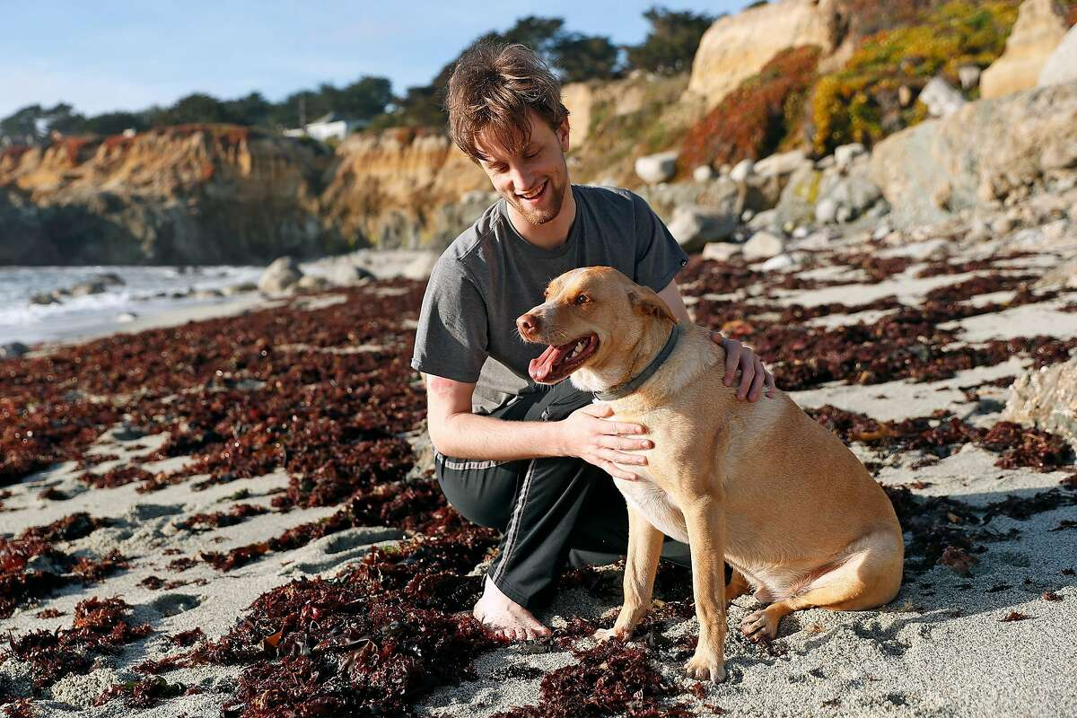 Nate Tyler and his dog, Opus, in Moss Beach, Calif., on April 29, 2021. Tyler, 24, did not want to get vaccinated, but It took both of his parents, one a pulmonary physician in a Kaiser ICU, and the other a retired doctor who specialized in HIV/AIDS, to persuade him to do it.