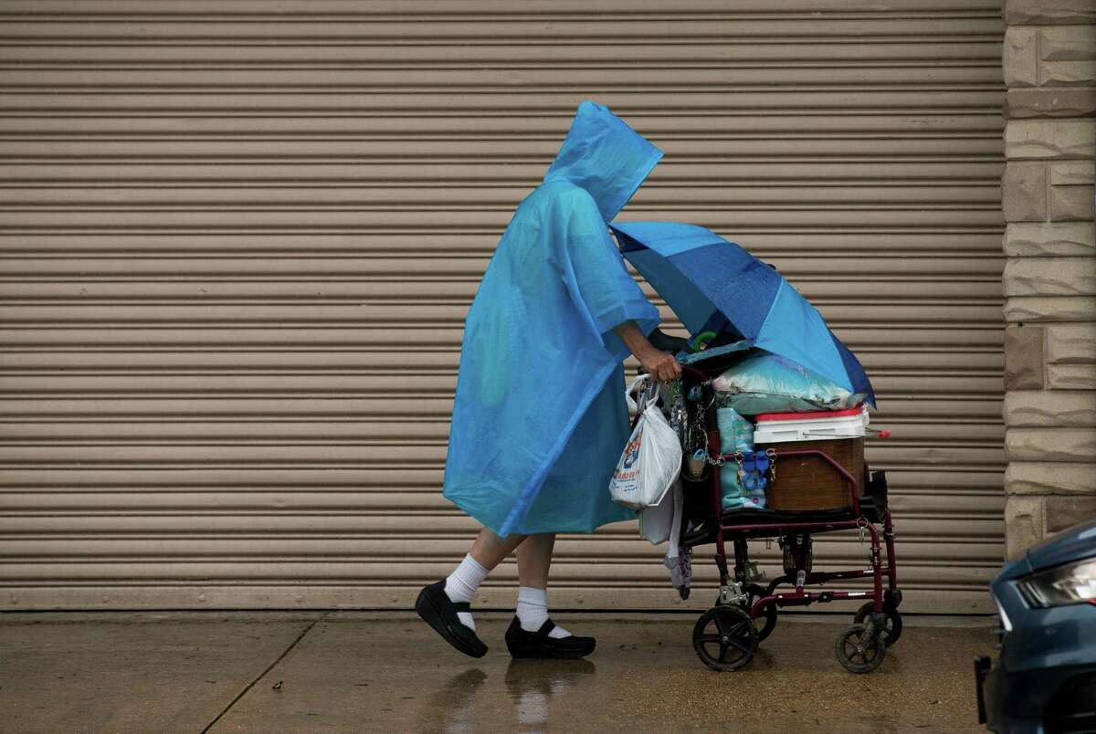 A pedestrian pushes a walker during a rain storm on Westheimer Road, on Friday, April 30, 2021, in Houston.