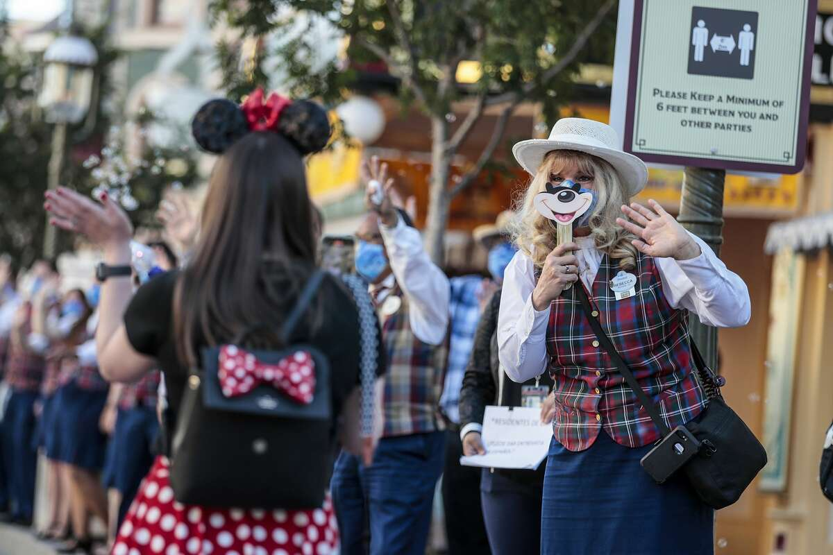 The first park visitors are greeted by cast members inside Disneyland as the theme park reopens for the first time in more than a year on Friday, April 30, 2021.