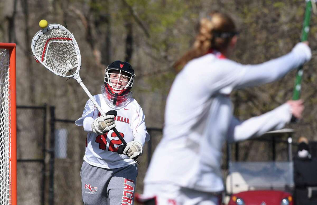 New Canaan goalie Claire Mahoney clears the ball during the Rams' girls lacrosse game against Darien at Dunning Field on Thursday, April 22, 2021.