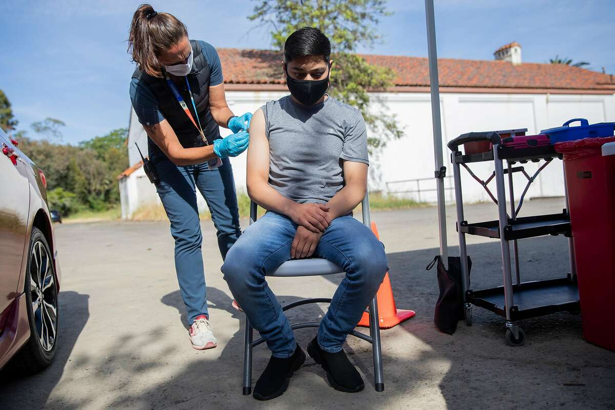 Registered nurse Becky Dodds prepares to give Kelver Vasquez of Ignacio his first dose of the Moderna COVID-19 vaccine at a Curative vaccination pop-up in the parking lot of Hamilton Community Center in Novato, Calif. Friday, April 30, 2021.