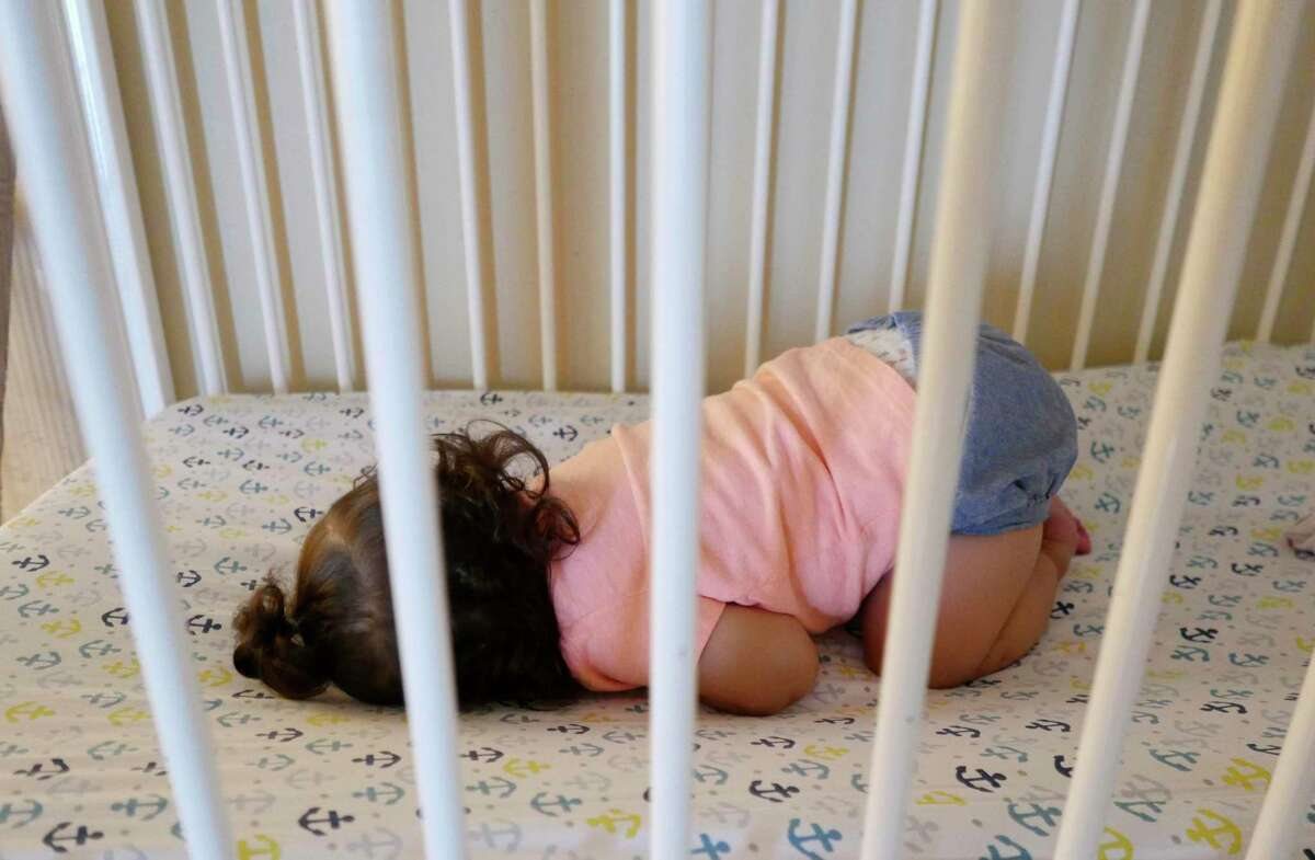 A child sleeps at the Children's Shelter of San Antonio in 2018. The child welfare system in Texas is in crisis and demands an emergency session.