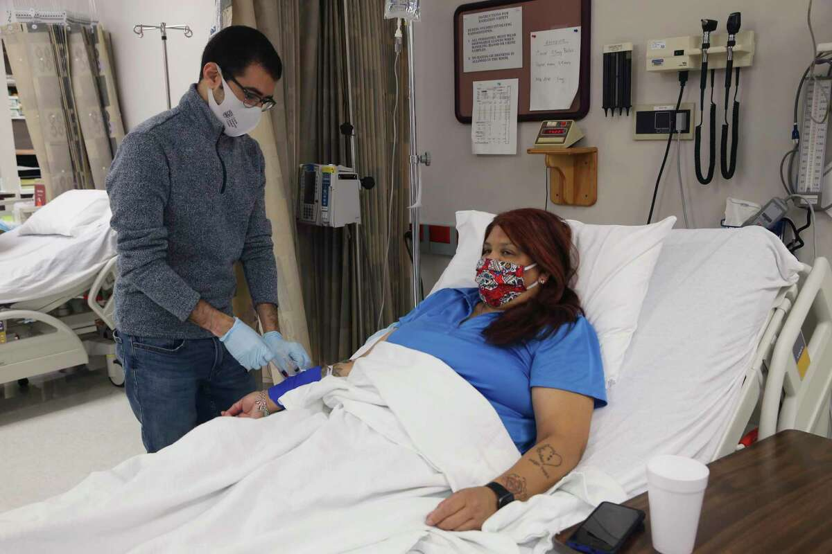 Research fellow Mohamed Eletrebi, 29, draws blood from Melissa Mata, 55, for glucose testing at the Texas Diabetes Institute on April 30, 2021. On March 31, Mata underwent an experimental procedure that removed internal fat from around her intestines. It has already helped reverse the effects of her Type 2 diabetes.