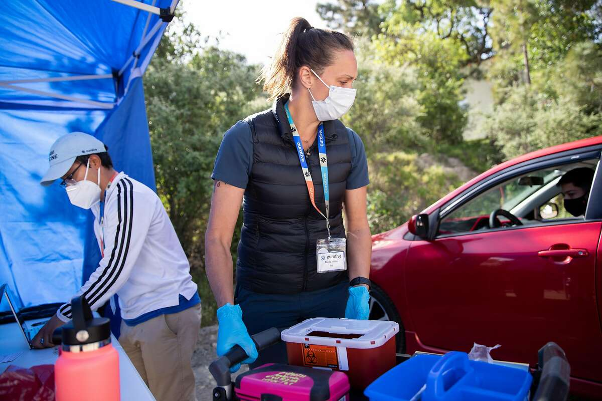 Field operations employee Pablo Cortez (left) and registered nurse Becky Dodds prepare to give Kelver Vasquez of Ignacio his first dose of the Moderna COVID-19 vaccine at a Curative pop-up clinic in the parking lot of Hamilton Community Center in Novato on Friday, April 30, 2021.