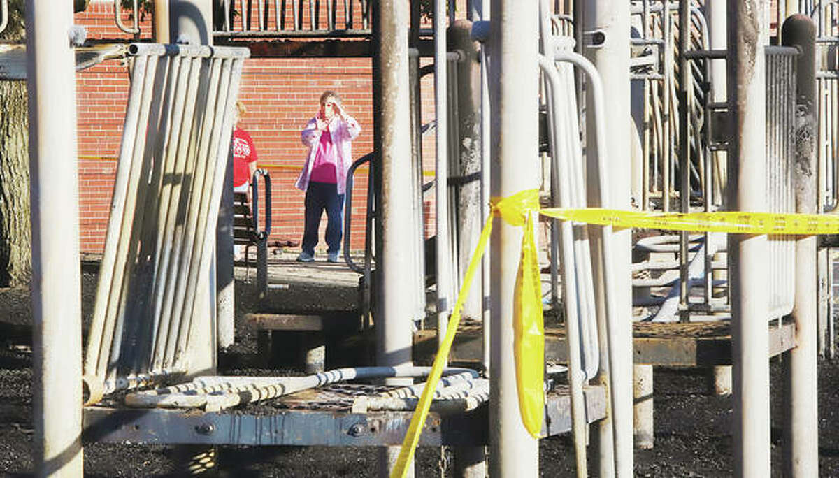 School staff were taking pictures of the damage done early Friday morning to the playground equipment behind West Elementary School following a fire in the rubber mulch surrounding the equipment.