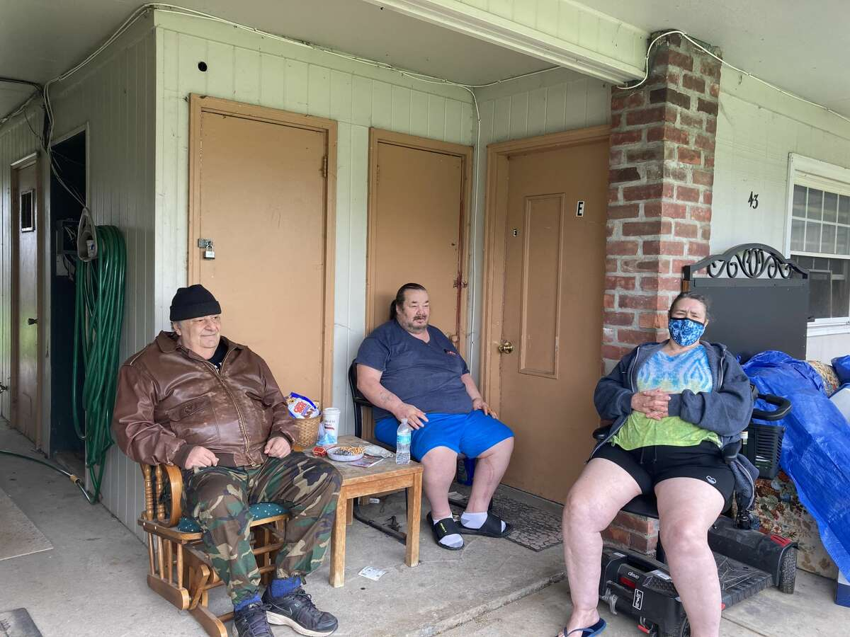 From left, Michael Cammisa, Robert Harrington and Linda Harrington sit outside their efficiency apartments at 43-45 Allen Drive. Cammisa said if there is a fire, there is a hose in the shared entryway. It can be seen behind him.