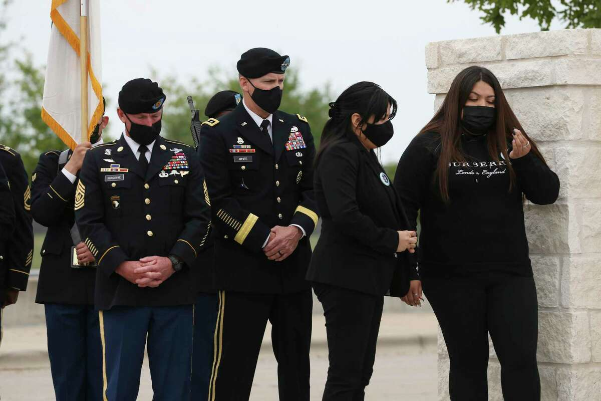 Lupe Guillen, second from right, and her sister, Mayra, stand by a sign at an entrance to Fort Hood renamed in honor of their sister, Spc. Vanessa Guillen, last week. On the left is Fort Hood Command Sgt. Maj. Arthur Burgoyne and Lt. Gen. Pat White.