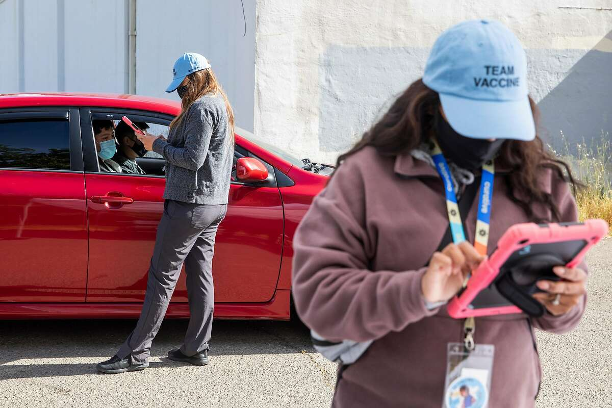 Sarah Milum checks in Kevin Vasquez of Ignacio before he receives his COVID-19 vaccine at a Curative pop-up clinic in the parking lot of Hamilton Community Center in Novato.