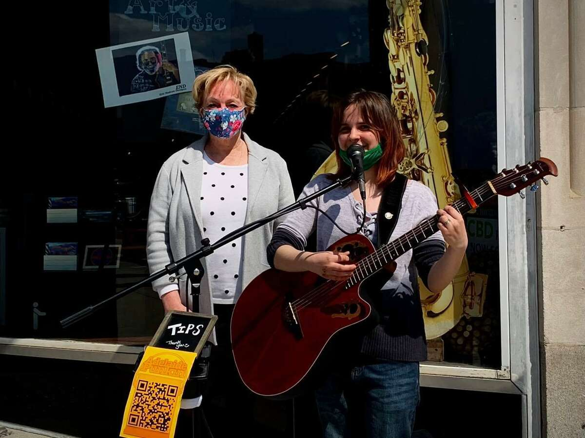 Performer Adelaide Punkin, whose parents, Alex and Veronica Datzek of Burlington, plays in front of the family's new gallery and store on Main Street, Art Life Culture. She was joined for the grand opening by Torrington Mayor Elinor Carbone.