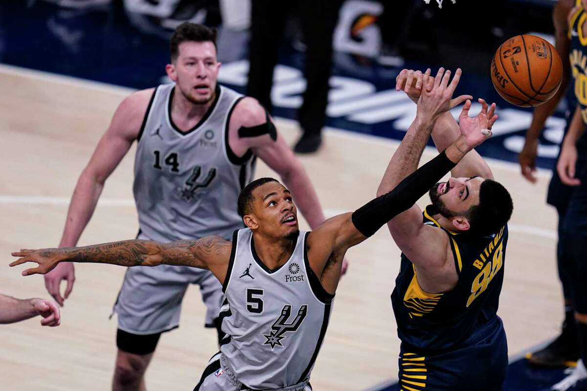 San Antonio Spurs guard Dejounte Murray (5) goes up for a rebound over Indiana Pacers center Goga Bitadze (88) during the second half of an NBA basketball game in Indianapolis, Monday, April 19, 2021. (AP Photo/Michael Conroy)