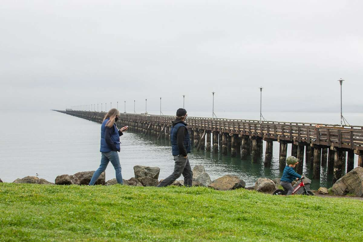 A family strolls past the closed Berkeley Pier on Feb. 19.