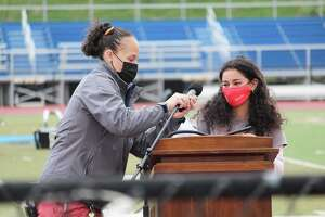 Middletown High School seniors, who have not fully gathered together since before the pandemic, celebrated college acceptance day Friday morning on the athletic field. Class president Ani Zakarian, right, gets a little help with the microphone before she addressed her classmates.