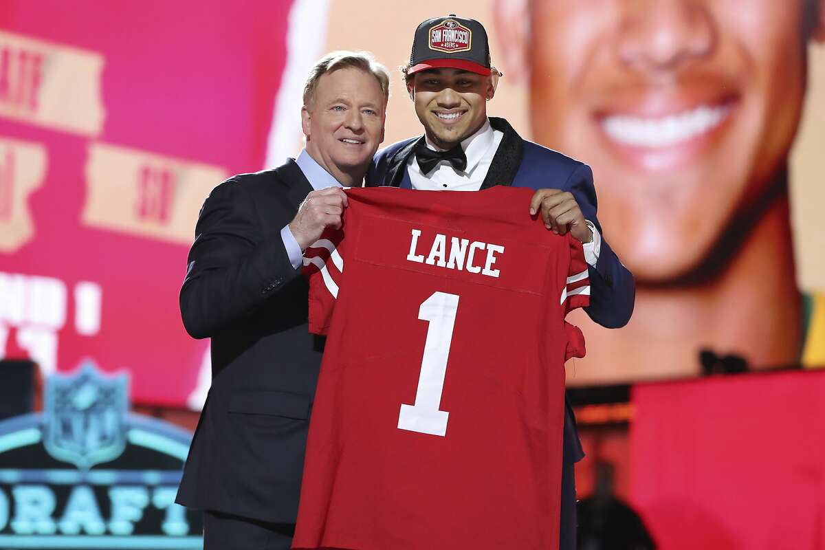 North Dakota State quarterback Trey Lance, right, holds a team jersey with NFL Commissioner Roger Goodell after the San Francisco 49ers selected Lance with the 3rd pick in the first round of the NFL football draft Thursday April 29, 2021, in Cleveland. (AP Photo/Gregory Payan)