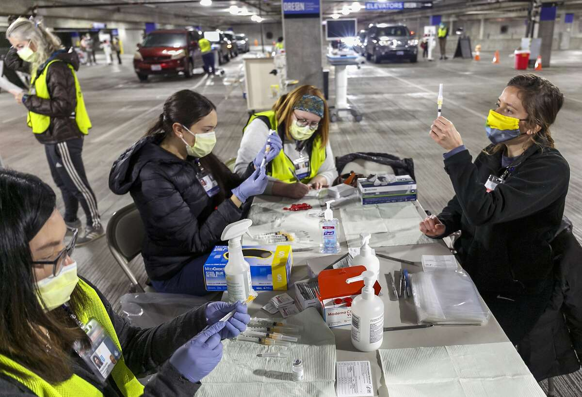 Medical professionals from Oregon Health & Science University load syringes with the Moderna COVID-19 vaccine at a drive-thru vaccination clinic in Portland, Ore., on Jan. 10, 2021.