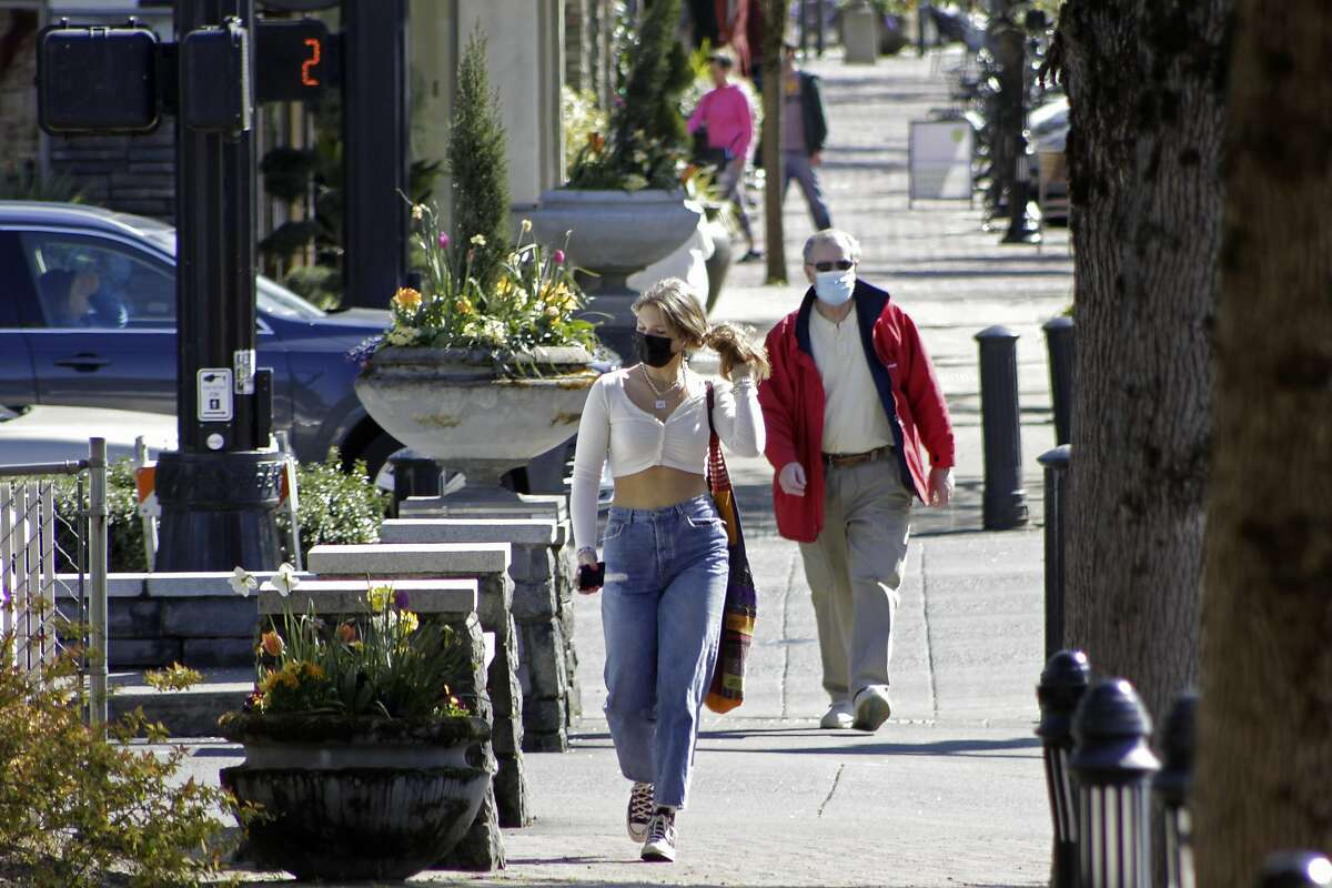 Residents wearing masks walk in downtown Lake Oswego, Ore., on Sunday, April 11, 2021.