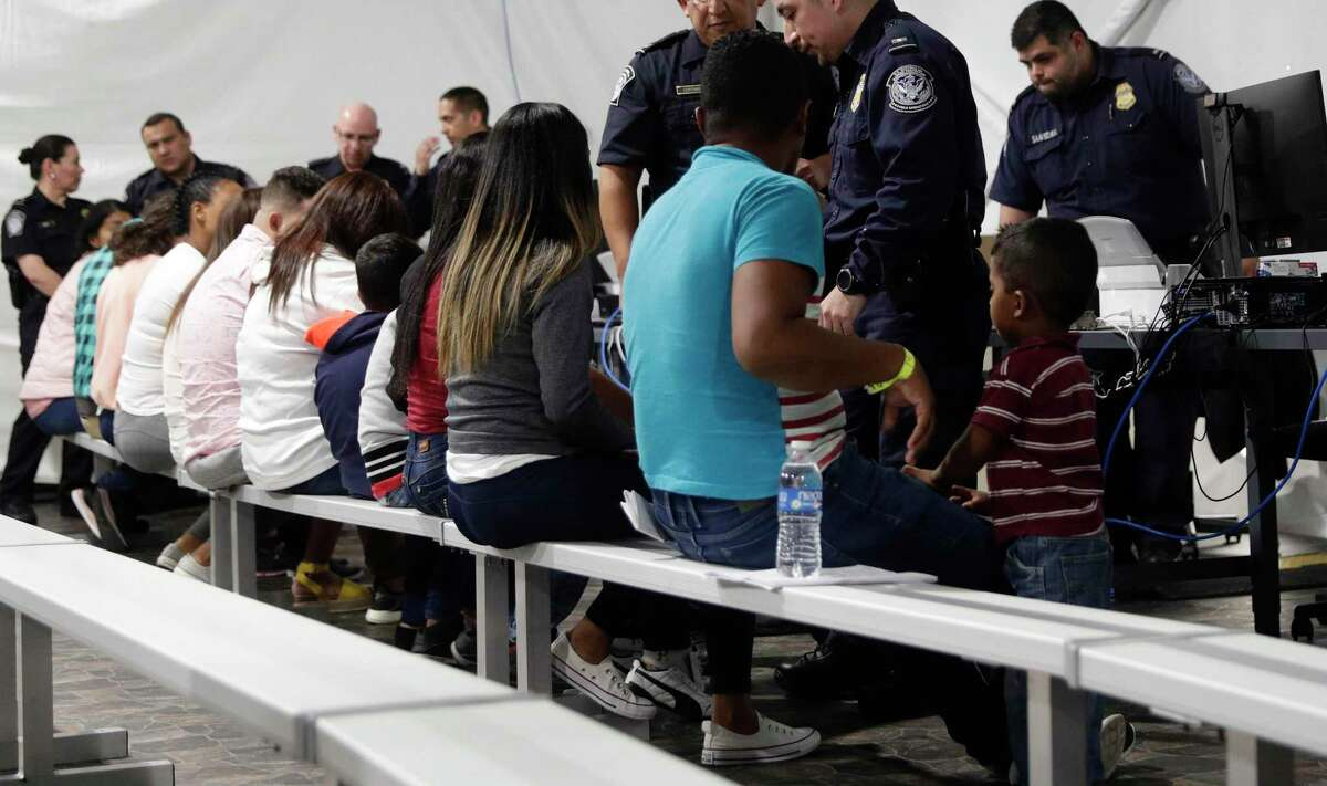 """Migrants apply for asylum at the Migration Protection Protocols Immigration Hearing Facility in Laredo in 2019. President Joe Biden signed an executive order this month instructing federal agencies to stop using the term """"alien"""" to describe non-citizens - a small but meaningful step in treating migrants respectfully."""
