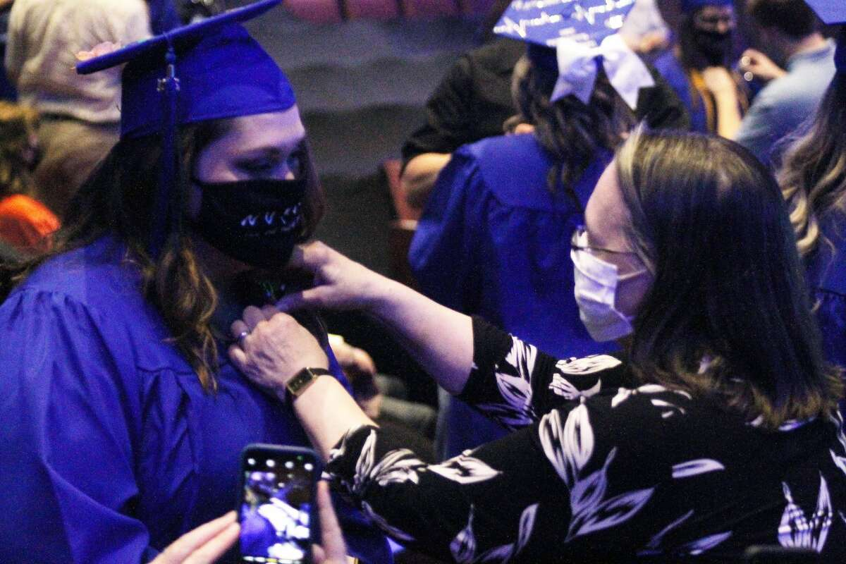 A West Shore Community College nursing graduate receives her pin. In order to mitigate the spread of the coronavirus, graduates were pinned by a guest of their choosing.