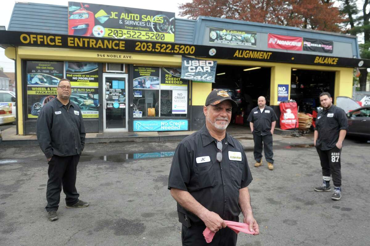 """Juan """"JC"""" Fernandez stands with three of his mechanics, from left, Anthony Miranda, Joey Colon and Edwin Maldonado, at JC Auto Sales and Service, in Bridgeport, Conn. April 29, 2021."""