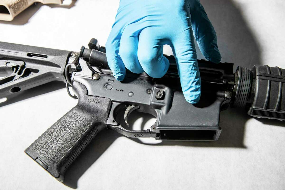 This file photograph shows a police service technician with the Oakland Police Department Property and Evidence Unit pointing to a seized AR-15 assault rifle from a sample of ghost guns, or unregistered and untraceable firearms, at the department's headquarters in Oakland, California Thursday, April 15, 2021.