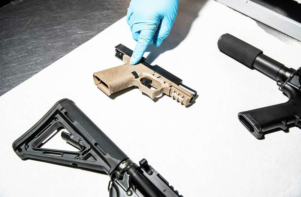 """An Oakland Police Department service technician displays unregistered and untraceable firearms, known as """"ghost guns."""""""