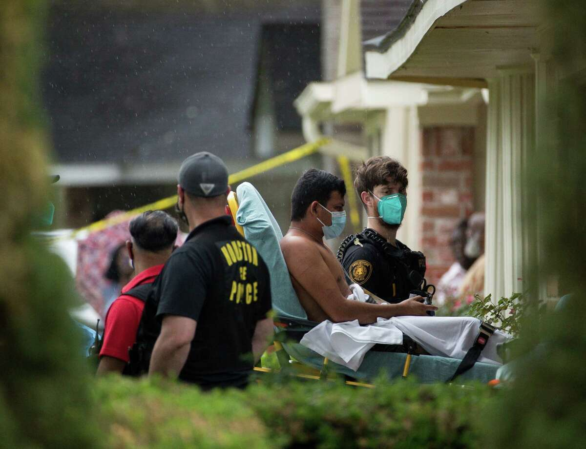 Paramedics transport a man into an ambulance from the scene of a human smuggling case, where more than 90 undocumented immigrants were found inside a home on the 12200 block of Chessington Drive on Friday, April 30, 2021, in Houston. A Houston Police official said the case will be handled by federal authorities and that some of the people inside the house were exhibiting COVID-19 symptoms.