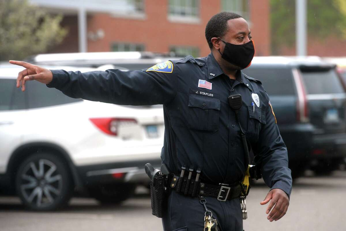 Shelton Police Officer John Staples directs traffic as school lets out at Perry Hill School, in Shelton, Conn. April 29, 2021.
