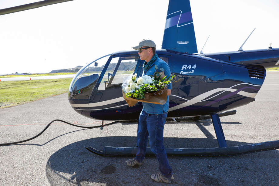 Eric Jones carries a bouquet of flowers to a helicopter in March before the second leg of a chartered flight to search for the boy's body. Photo: Gabrielle Lurie, The Chronicle