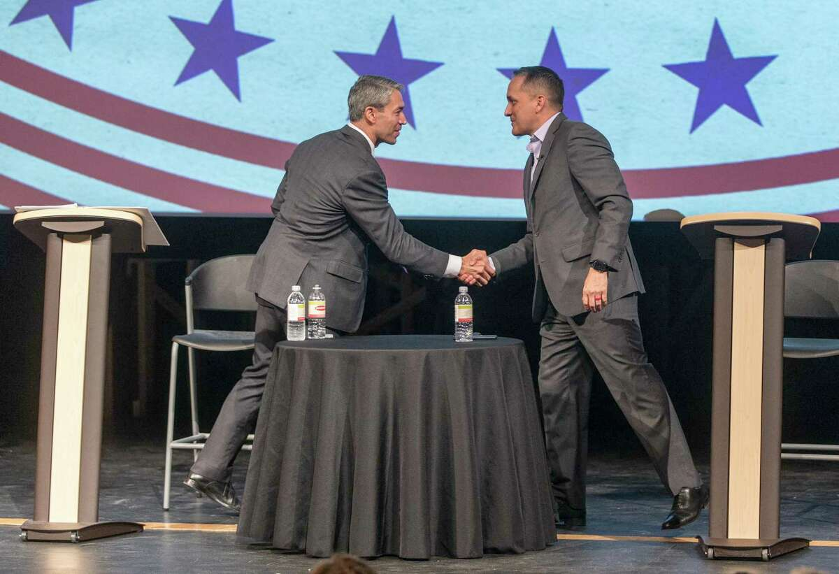 Mayor Ron Nirenberg, left, and Councilman Greg Brockhouse shake hands after participating in a 2019 forum. San Antonio's mayoral and City Council races are nonpartisan.