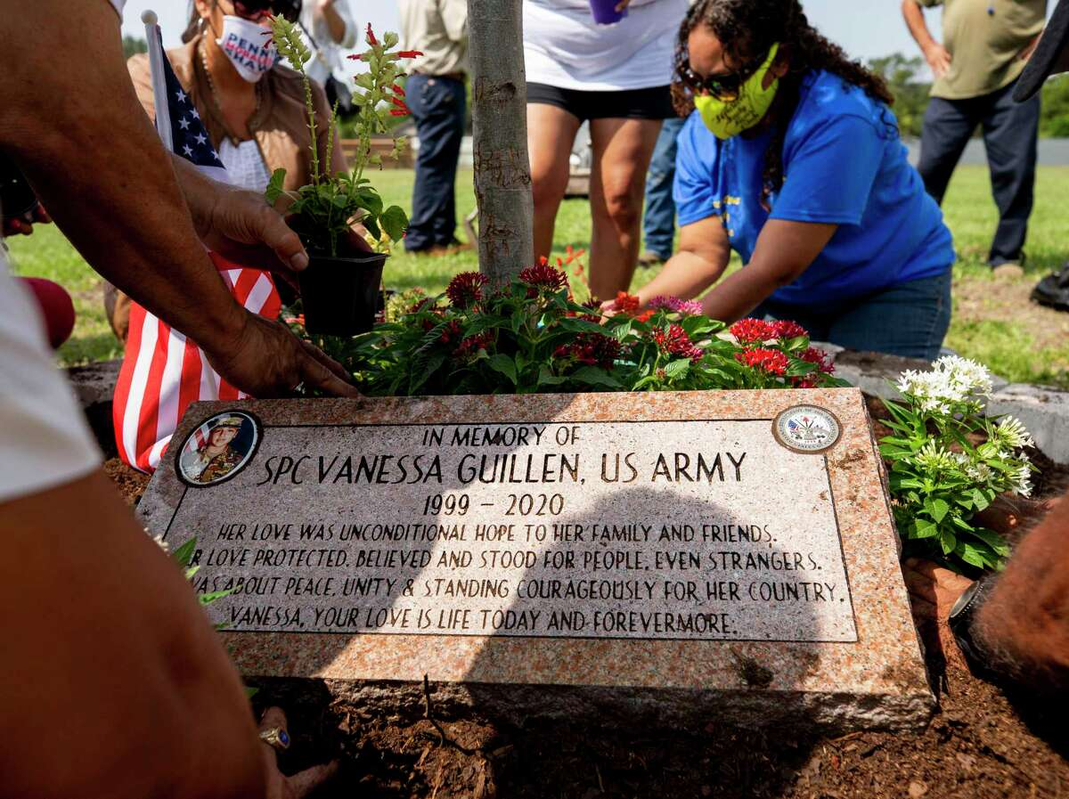 Members of Gathering of Eagles, a local veterans group, and community members work to plant flowers around a planted tree to honor Houston native Pfc. Vanessa Guillen, at Veterans Memorial Park on Saturday, Sept. 19, 2020, in Houston.