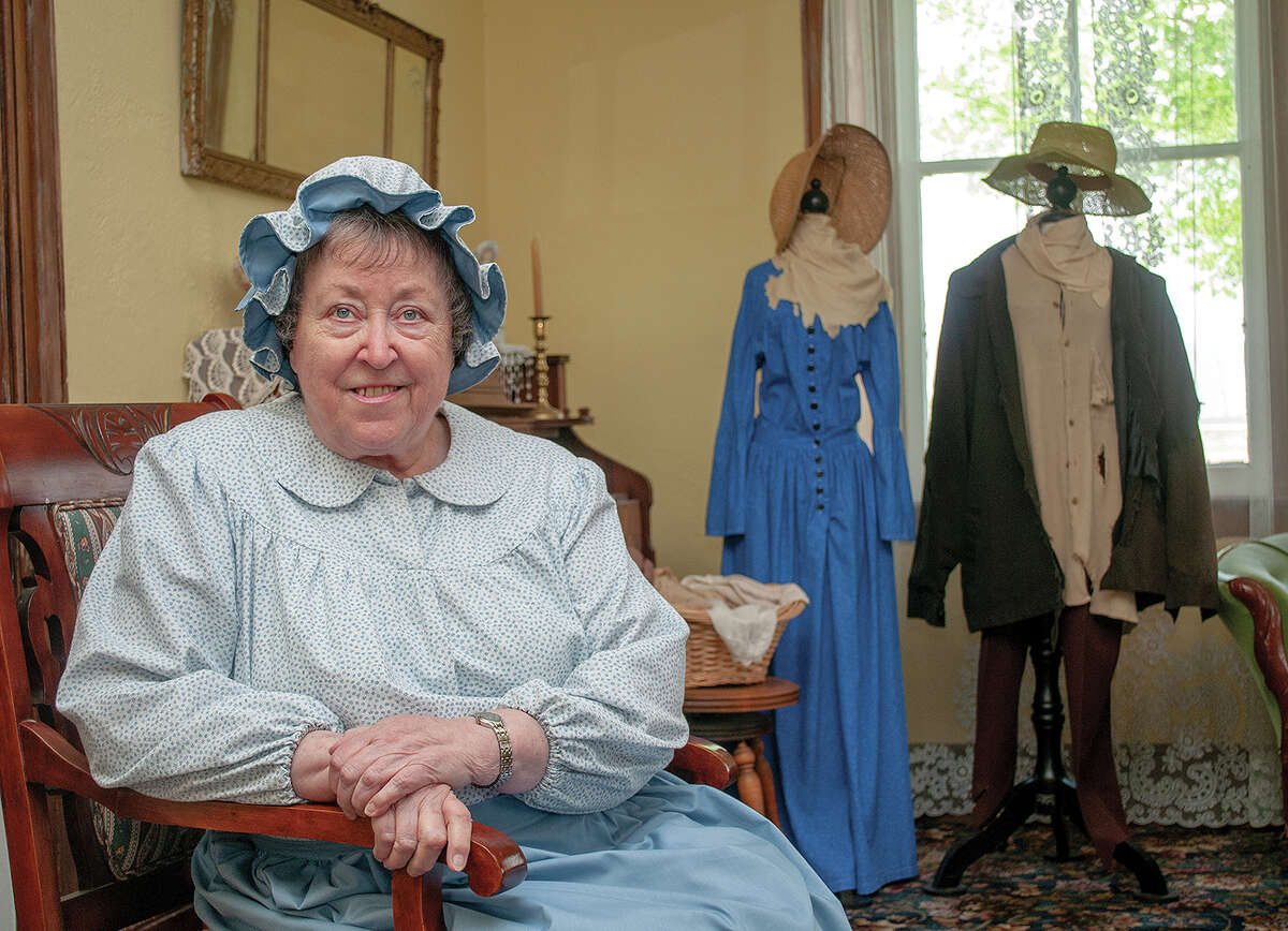 Volunteer Barbara Suelter wears clothing of the 1800s as she sits in the parlor at Woodlawn Farm. Suelter is excited that limited tours of the historic farm are set to begin June 1. The farm has been closed because of the COVID-19 pandemic.