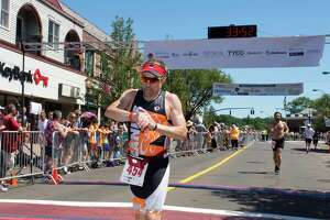 Branford's Alan Mcdougall, pictured here crossing the finish line at the Branford Road Race, is adjusting to competing in virtual road races. The Branford Road Race, held each Father's Day since 1979, will be virtual this year.