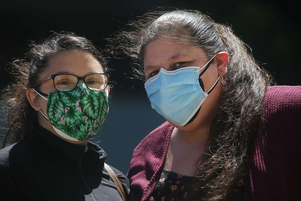 Laurina Marcic (right) and her sister Stephanie Marcic (left) stand for a portrait on Tuesday, April 27, 2021 in San Francisco, Calif. Laurina Marcic is vaccinated as are the adults she lives with but is still follwing safety precautions because she is worried about the family members she lives with such as her nephew who is too young to be vaccinated and aunt who is immune compromised.