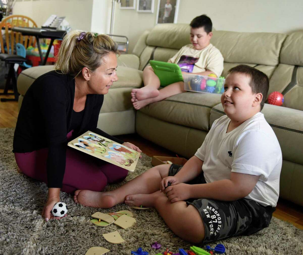 Timea Zadori cares for her two children, Noah, center, 9, and Noel, right, 10, at her apartment in Greenwich, Conn. Wednesday, April 21, 2021. Zadori quit her job during the pandemic to care for her two nonverbal sons on the autism spectrum that require constant attention and assistance.