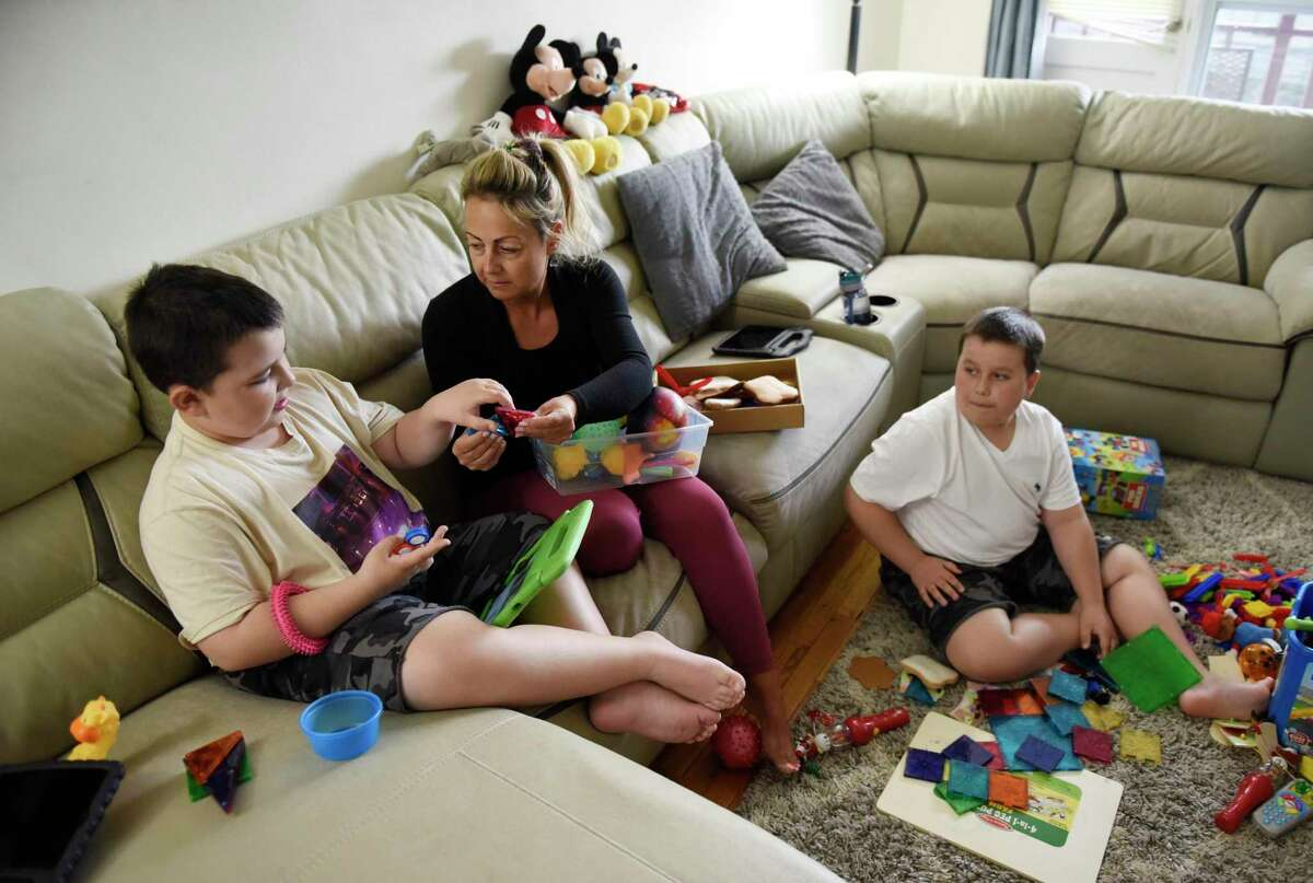 Timea Zadori cares for her two children, Noah, left, 9, and Noel, 10, at her apartment in Greenwich, Conn. Wednesday, April 21, 2021. Zadori quit her job during the pandemic to care for her two nonverbal sons on the autism spectrum that require constant attention and assistance.