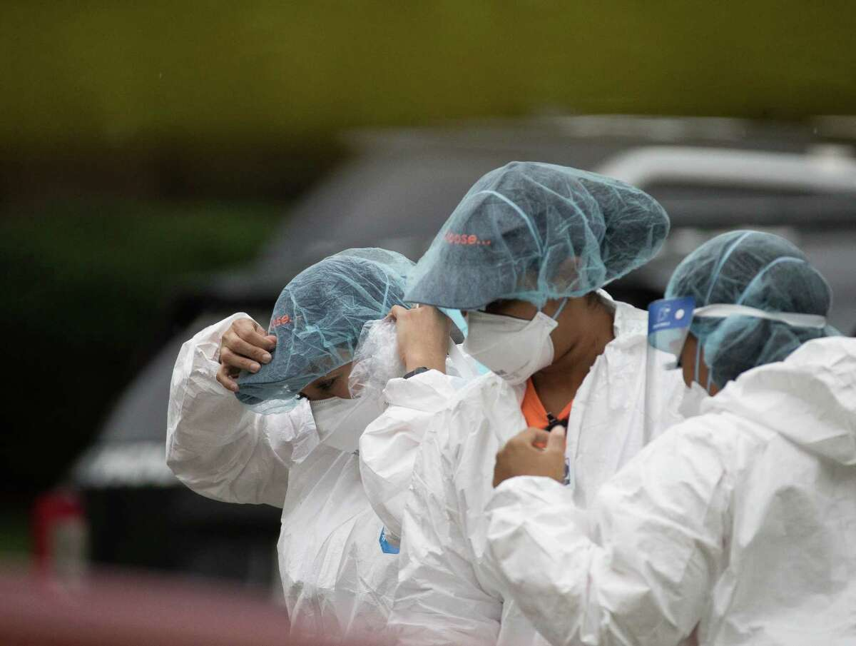 A team dons PPE before entering the home where more than 90 undocumented immigrants were found on the 12200 block of Chessington Drive on Friday, April 30, 2021, in Houston. A Houston Police official said the case will be handled by federal authorities and that some of the people inside the house were exhibiting COVID-19 symptoms.