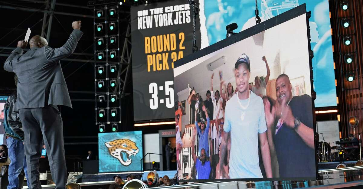 Former Jacksonville Jaguar Kevin Hardy raises his arms as an image of Georgia cornerback Tyson Campbell is displayed during the second round of the NFL football draft, Friday, April 30, 2021, in Cleveland. The Jaguars selected Campbel(AP Photo/Tony Dejak)