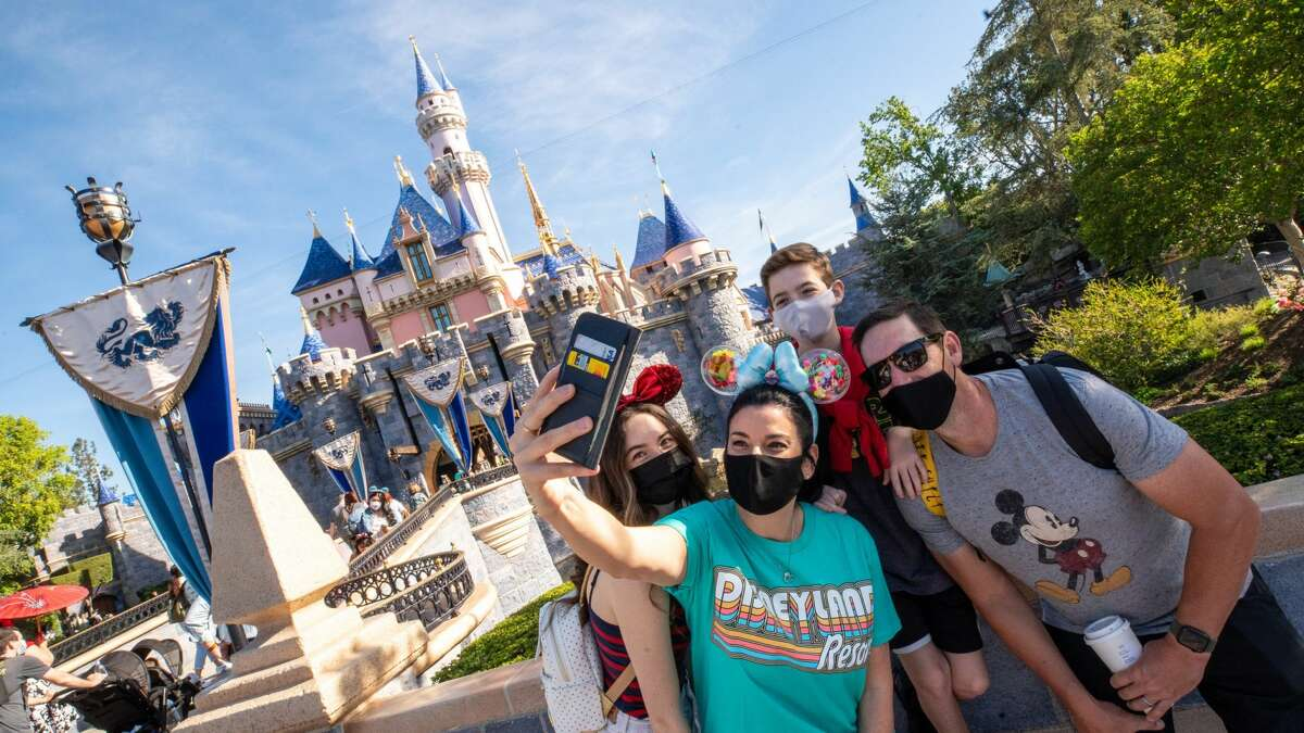 The Wotter family of Lake Elsinore, Calif., captures a special moment in front of Sleeping Beauty Castle as Disneyland Park in Anaheim, Calif., reopens Friday, April 30, 2021.