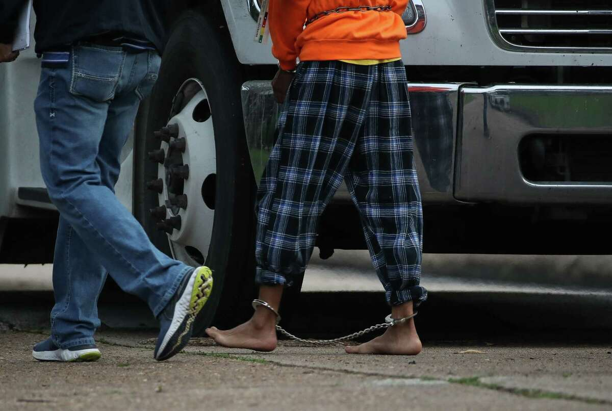 An undocumented migrant is ushered into a bus from the scene of a human smuggling case, where more than 90 undocumented migrants were found inside a home on the 12200 block of Chessington Drive, on Friday, April 30, 2021, in Houston. A Houston Police official said the case will be handled by federal authorities.