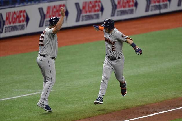 ST PETERSBURG, FLORIDA - APRIL 30: Alex Bregman #2 of the Houston Astros celebrates with third base coach Omar Lopez #22 after hitting a two run home run during the third inning against the Tampa Bay Rays at Tropicana Field on April 30, 2021 in St Petersburg, Florida. (Photo by Douglas P. DeFelice/Getty Images) Photo: Douglas P. DeFelice/Getty Images / 2021 Getty Images
