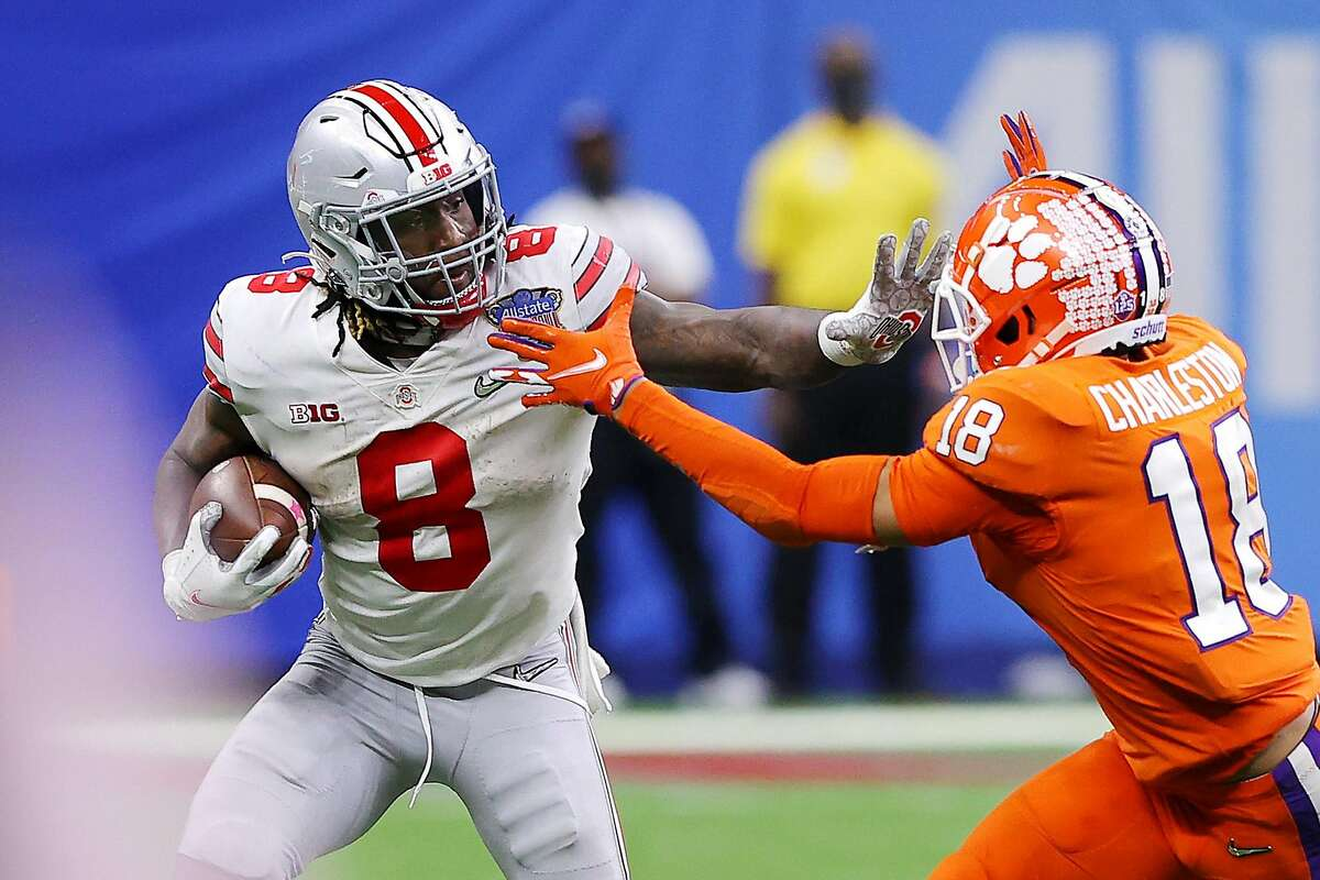 NEW ORLEANS, LOUISIANA - JANUARY 01: Trey Sermon #8 of the Ohio State Buckeyes stiff arms Joseph Charleston #18 of the Clemson Tigers in the second half during the College Football Playoff semifinal game at the Allstate Sugar Bowl at Mercedes-Benz Superdome on January 01, 2021 in New Orleans, Louisiana. (Photo by Kevin C. Cox/Getty Images)