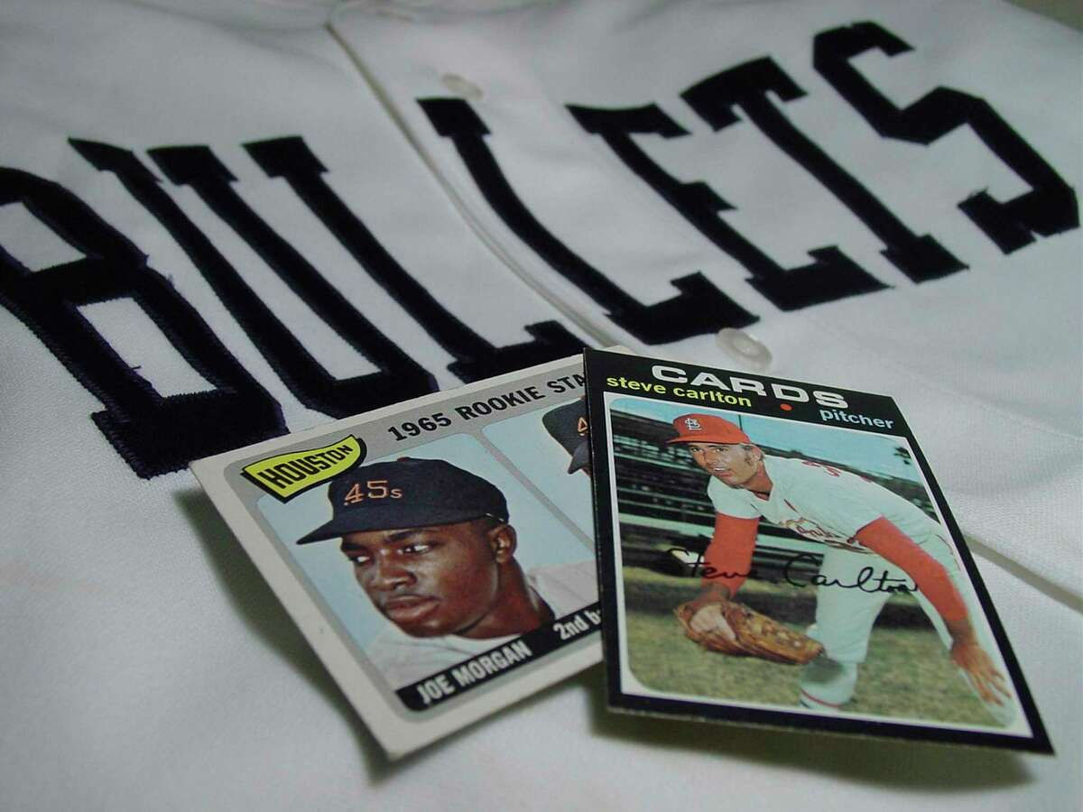 A 1965 Topps Joe Morgan card and 1971 Topps Steve Carlton card rest on a San Antonio Bullets jersey. The San Antonio minor league baseball team was affiliated for two seasons with the Houston Colt .45s, which later became the Astros. Future Hall of Famer Morgan was among the Bullets' star players. At that same time, Carlton, a future Cardinals star, pitched in the Texas League.