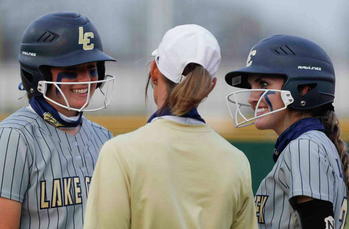FILE - Lake Creek's Payton Bauer, right, and Ava Brown smile as they visit with head coach Michelle Rochinski smiles during a break in the second inning of a high school softball game at Lake Creek High School, Tuesday, March 16, 2021, in Montgomery.
