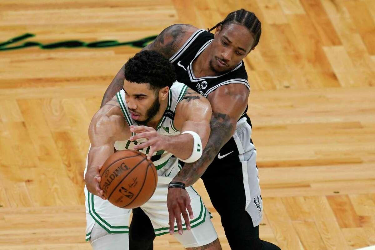 San Antonio Spurs forward DeMar DeRozan reaches in to defend against Boston Celtics forward Jayson Tatum during the second half of an NBA basketball game Friday, April 30, 2021, in Boston. (AP Photo/Elise Amendola)