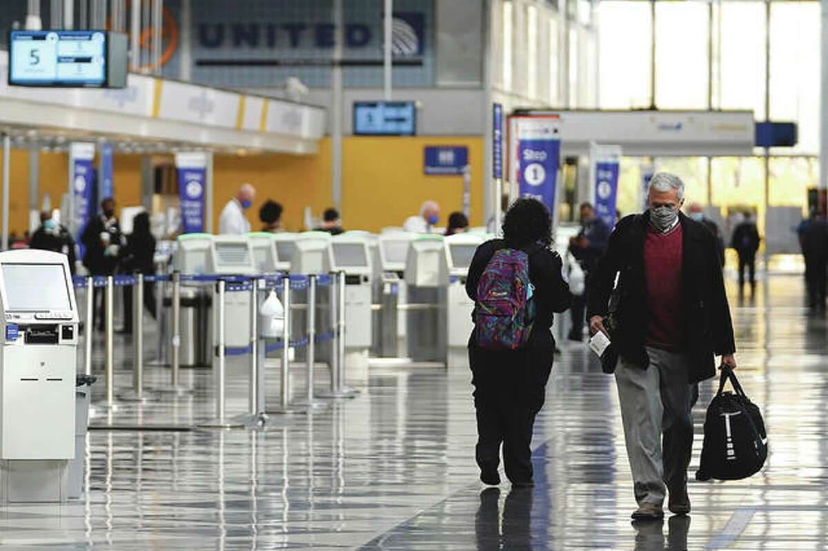 Travelers walk through Terminal 1 at O'Hare International Airport in Chicago. As vaccinations roll out, questions remain about how and where people can travel safely and on a budget this summer. Experts recommend first and foremost to get vaccinated before traveling and continue to follow guidance for COVID-19 safety even after being inoculated.