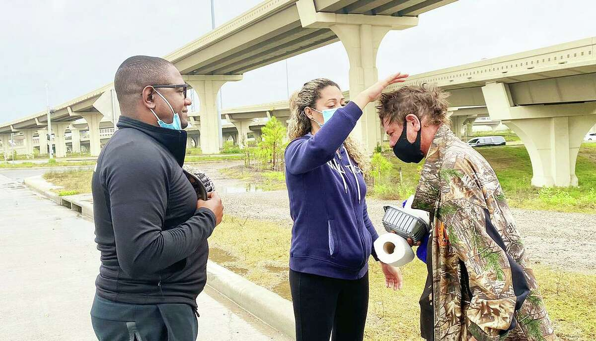 Corey Marshall watches as his wife Raquel lays hands on one of the homeless clients they helped alongside the freeway.