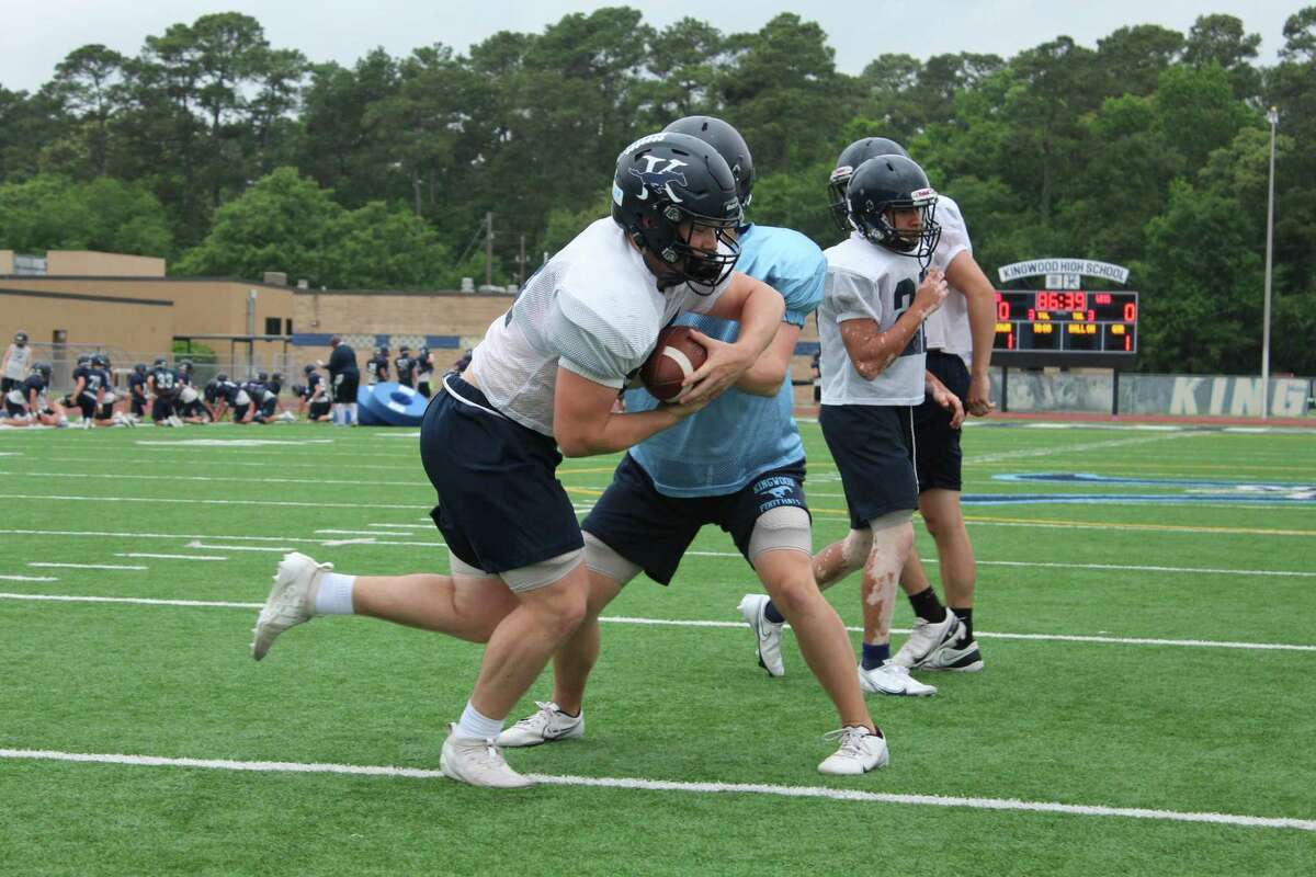 Kingwood running back Nick Bernell working with quarterback in a drill.